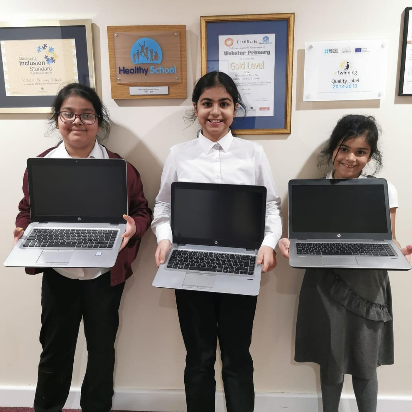 three primary school girls with holding donated laptops